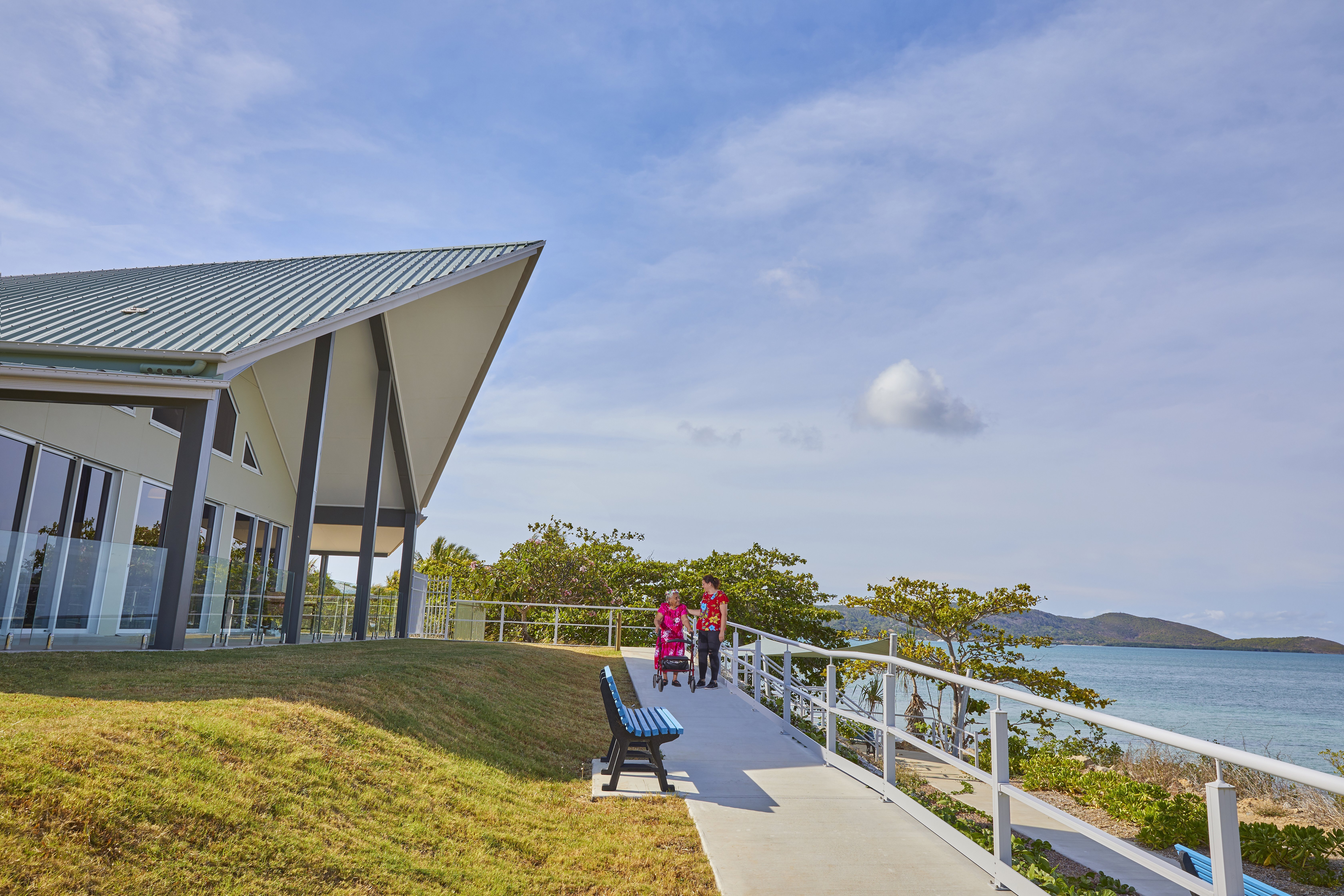 photo of staff and resident walking outside along the waterfront at the star of the sea nursing home on thursday island.